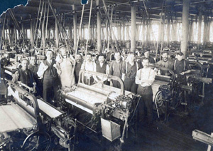 Men standing next to machines on mill work floor