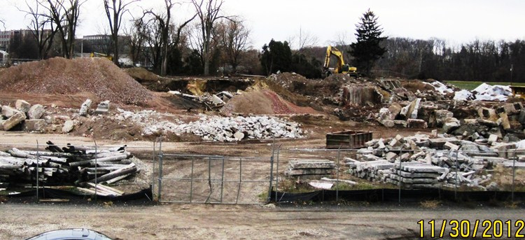 Excavator and mounds of debris in demolition work area