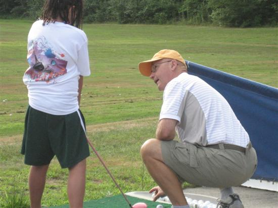 Instructor kneeling, showing camp participant technique tips