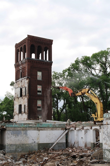 Excavator knocking down tower