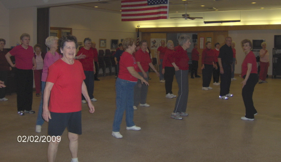 Participants in fitness class wearing red to support heart health