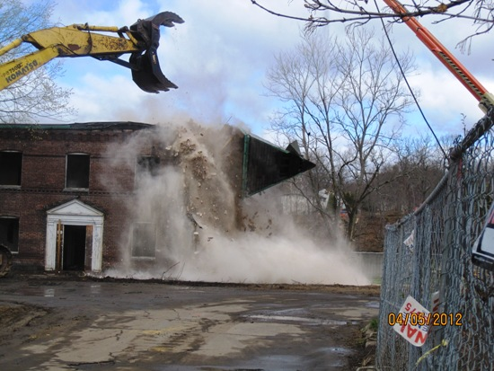 Excavator smashing roof of building